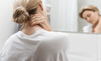 woman looking in mirror having neck pain